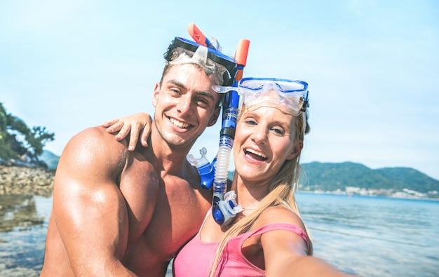 Paare, die selfie an den strandreiseferien nehmen