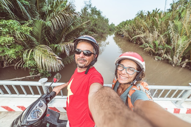 Paare, die selfie auf motorrad nehmen. mann und frau mit dem sturzhelm, der in die mekong-delta-region, süd-vietnam radfährt. üppiges grünes kokosnusspalmewaldland und wasserkanal.