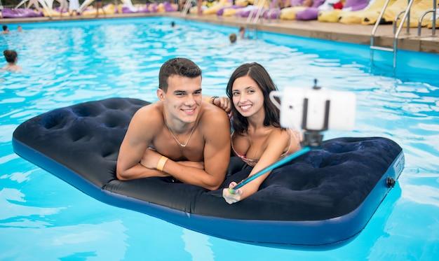 Paare, die selfie foto auf matratze im pool machen