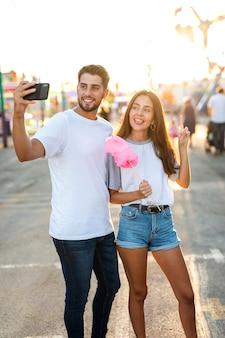 Paare, die selfie mit zuckerwatte nehmen