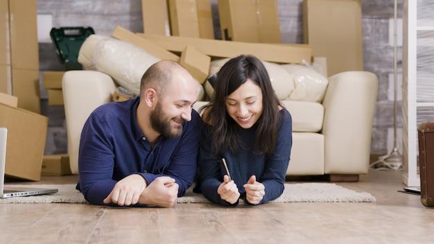 Paare, die sich auf dem boden ihrer neuen wohnung niederlegen. freund, der seiner freundin schlüssel gibt