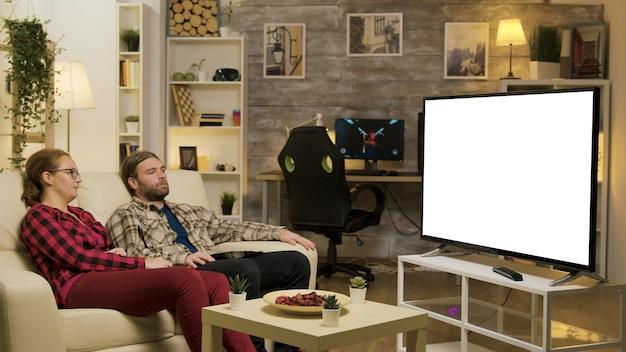 Paare, die sich auf dem sofa entspannen und im fernsehen mit grünem bildschirm gucken. aufnahme vergrößern.