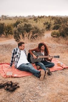 Paare, die sich draußen auf einer decke entspannen