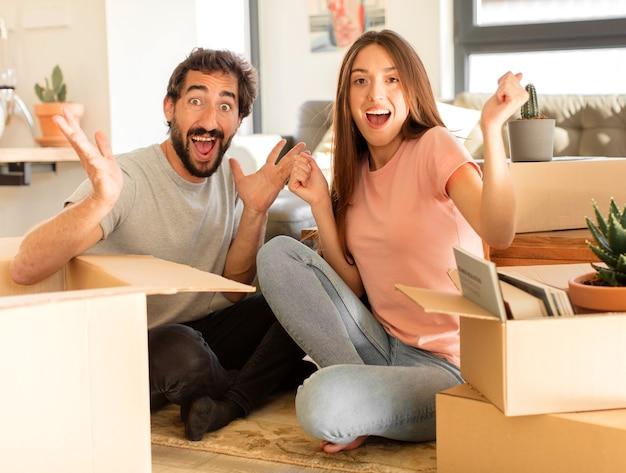 Paare, die sich glücklich, aufgeregt, überrascht oder schockiert fühlen, lächeln und über etwas unglaubliches erstaunt sind