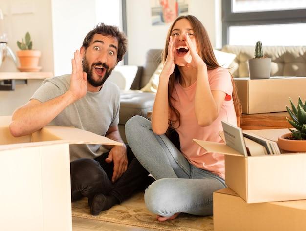 Paare, die sich glücklich, aufgeregt und positiv fühlen, mit den händen neben dem mund einen großen schrei aussprechen und schreien