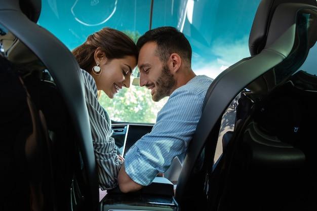 Paare, die sich glücklich fühlen. liebevolle gutaussehende paare, die sich glücklich fühlen, ein wochenende zusammen zu verbringen, während sie im auto sitzen