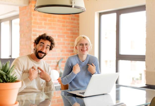 Paare, die sich glücklich, überrascht und stolz fühlen und mit einem aufgeregten, erstaunten blick auf sich selbst zeigen