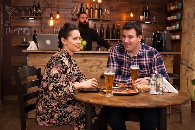 Paare, die sich im pub entspannen und pizza essen. sie lachen und essen pizza.