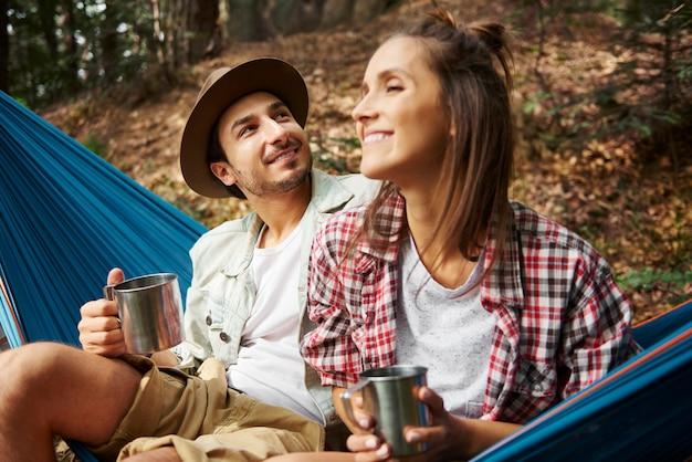 Paare, die sich in der hängematte im wald entspannen