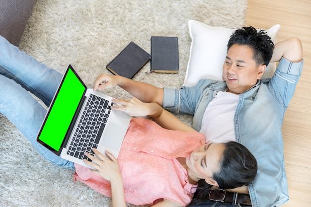 Paare, die sich unter verwendung des laptops hinlegen