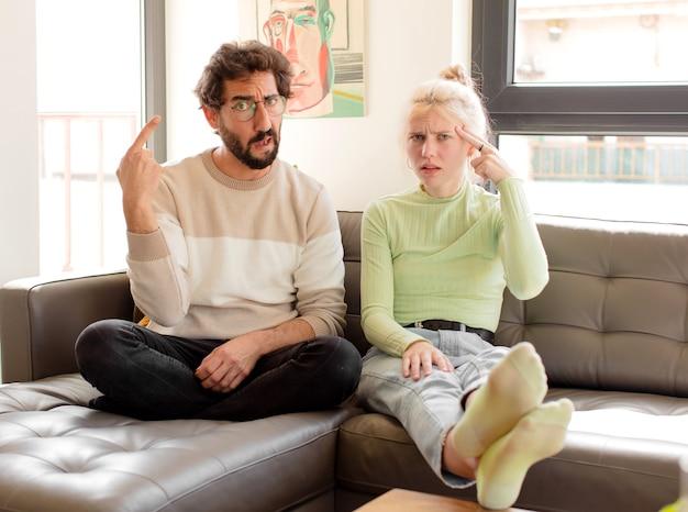 Paare, die sich verwirrt und verwirrt fühlen und zeigen, dass sie verrückt, verrückt oder verrückt sind