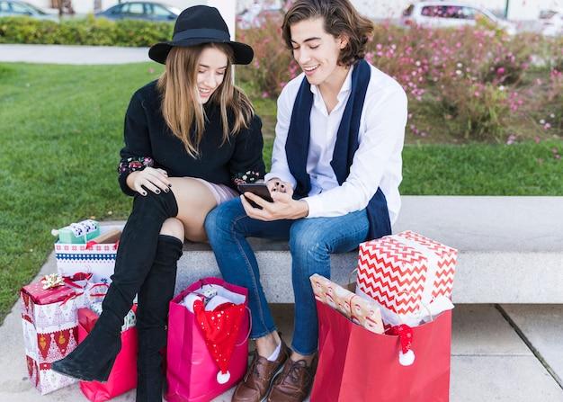 Paare, die smartphone auf bank betrachten