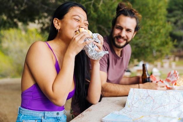 Paare, die snack bei tisch draußen essen