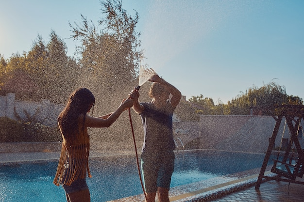 Paare, die spaß haben, gießen sich mit gartenschlauch