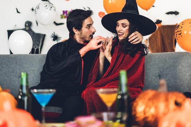 Paare, die spaß haben, kürbise zu halten und gekleidete karnevalshalloween-kostüme zu tragen