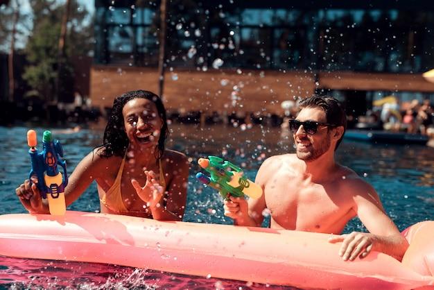 Paare, die spaß im swimmingpool haben