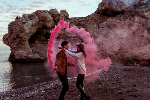 Paare, die spaß mit rauchbombe auf seeufer haben