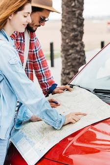 Paare, die straßenkarte auf rotem auto betrachten