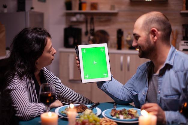 Paare, die tablet-pc mit chroma-key verwenden und ihre gemeinsame zeit beim romantischen abendessen genießen. mann und frau betrachten die chroma-key-anzeige der greenscreen-vorlage, die am tisch in der küche sitzt