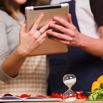 Paare, die tablette verwenden, während sanduhr eingeschaltet ist