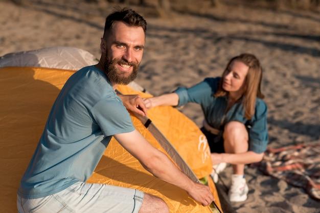 Paare, die tagsüber ein zelt aufbauen