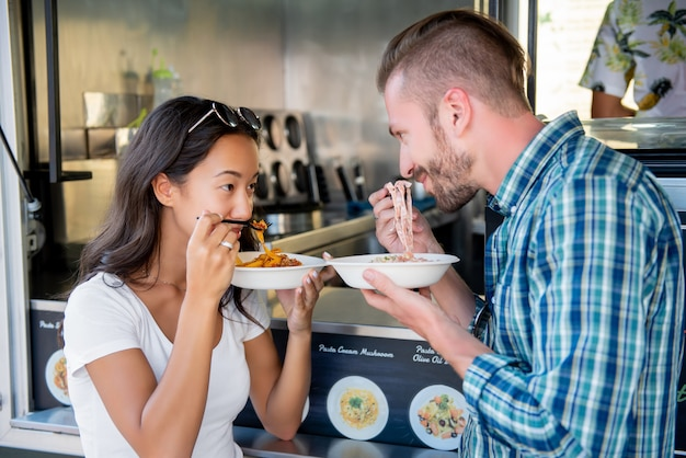 Paare, die teigwaren am lebensmittel-lkw essen