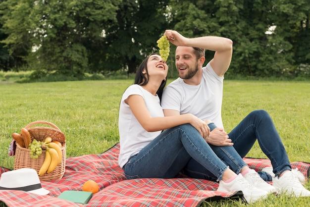 Paare, die trauben essen, legen eine picknickdecke herein