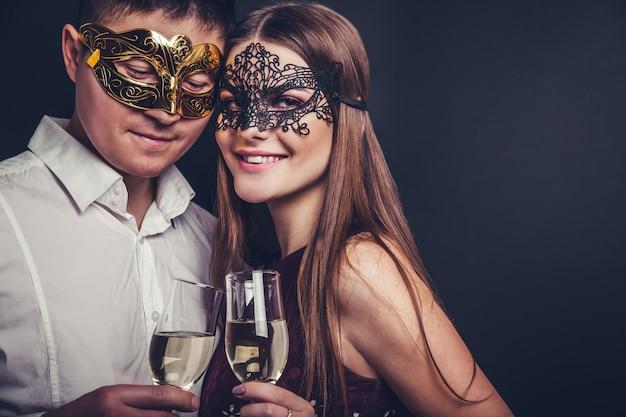 Paare, die trinkenden champagner des sylvesterabends auf maskeradepartei feiern