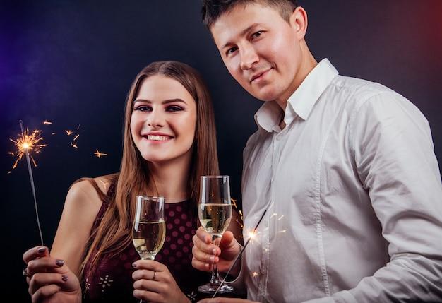 Paare, die trinkenden champagner des sylvesterabends feiern und wunderkerzen anzünden