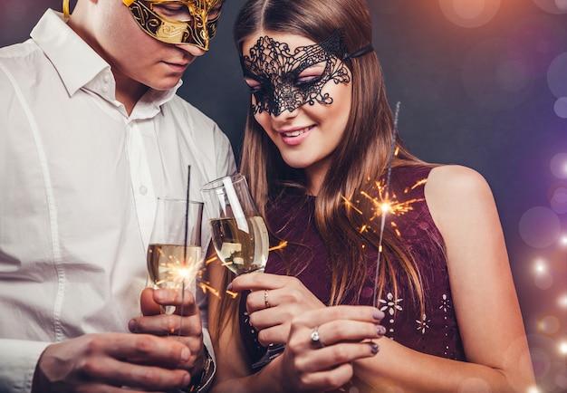 Paare, die trinkenden champagner des sylvesterabends feiern und wunderkerzen auf maskeradepartei leuchten