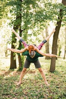 Paare, die übendes yoga der balance im park tun