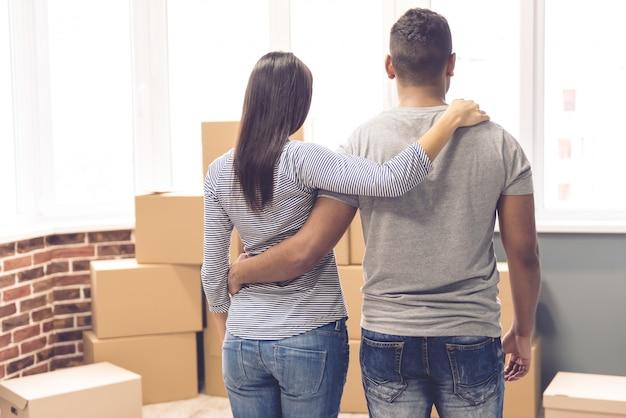 Paare, die verpackte kästen beim bewegen umarmen und betrachten