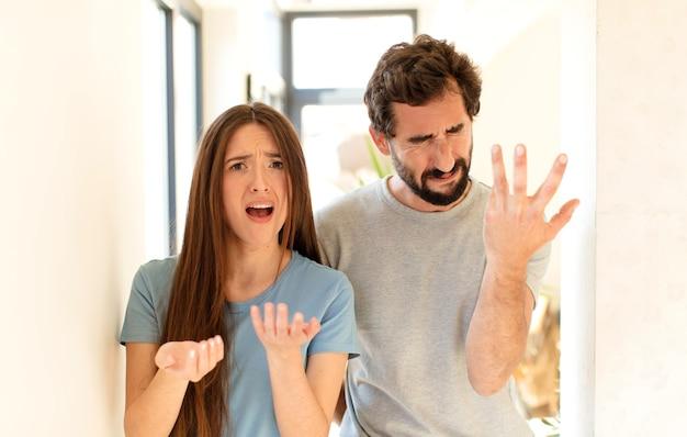 Paare, die verzweifelt und frustriert, gestresst, unglücklich und genervt aussehen, schreien und schreien