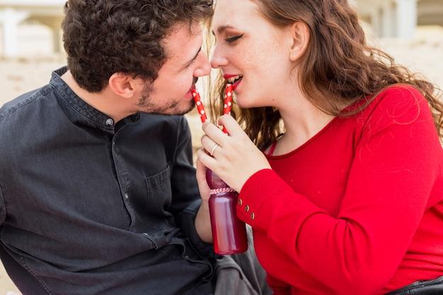 Paare, die von der flasche mit strohen trinken