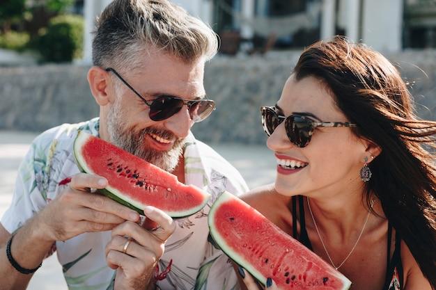 Paare, die wassermelone am strand essen