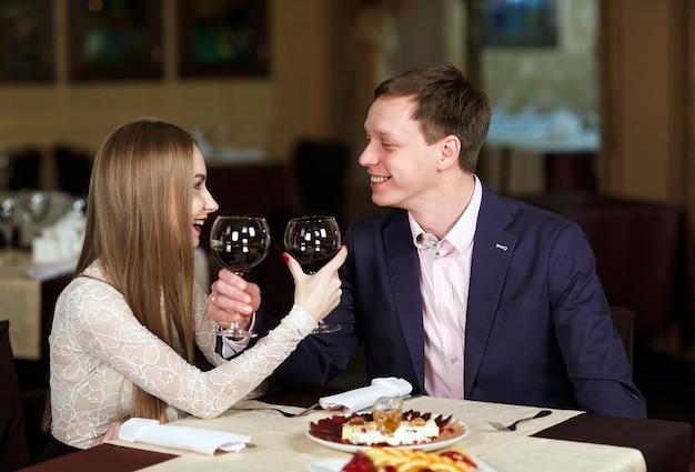 Paare, die weingläser in einem luxusrestaurant rösten.