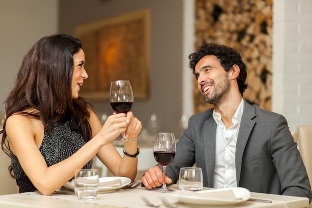 Paare, die weingläser in einem luxusrestaurant rösten