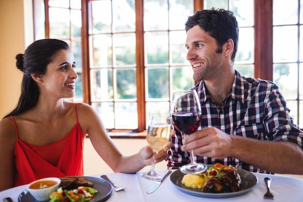 Paare, die weinglas am tisch im restaurant rösten