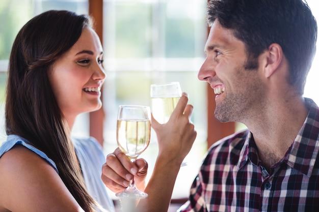 Paare, die weißwein im restaurant essen