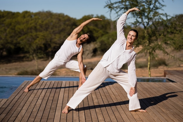 Paare, die yoga an den safariferien durchführen