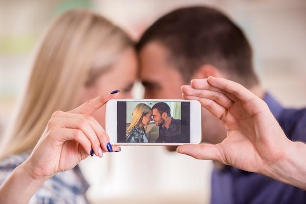 Paare, die zu hause auf der couch, unter verwendung des telefons sitzen