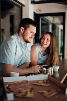 Paare, die zu hause kühlen und und pizza essen