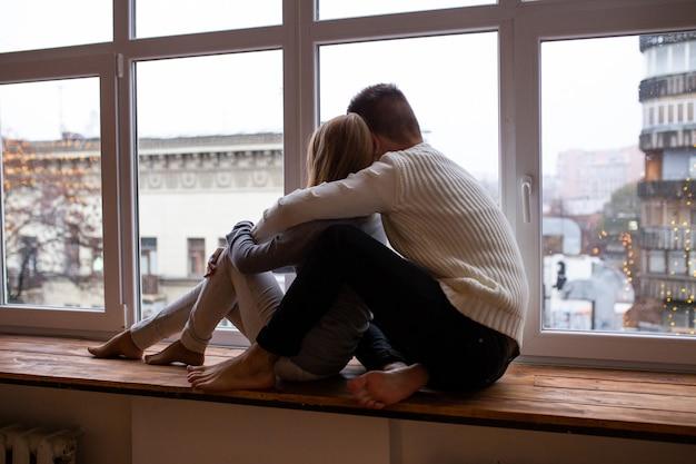 Paare, die zu hause nahe fenster sitzen
