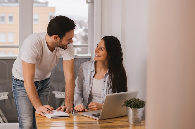 Paare, die zu hause zusammenarbeiten, einander betrachten und lächeln