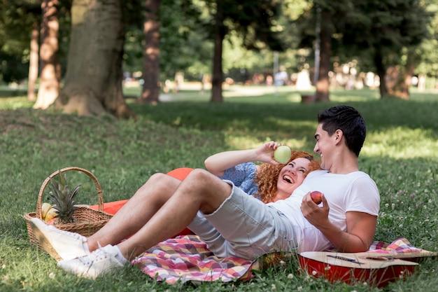Paare, die zusammen äpfel im park essen