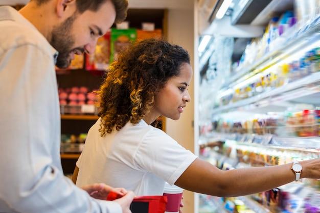 Paare, die zusammen an einem supermarkt kaufen