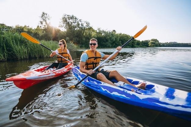 Paare, die zusammen auf dem fluss kayak fahren