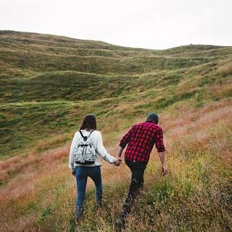Paare, die zusammen die hügel trekking sind