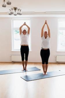 Paare, die zusammen eine yogahaltung tun