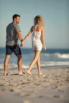 Paare, die zusammen hand in hand auf den strand gehen